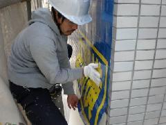 ビル壁面に広告シートを直貼り 施工中