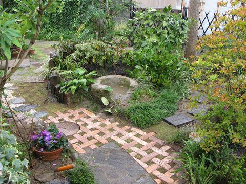 手づくりの庭にアクセント  (煉瓦パターン敷き 石臼 水鉢)