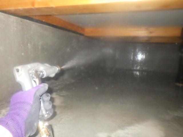 床下での薬剤散布作業中。
