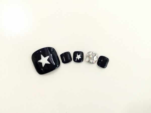 黒をベースにした星のフットネイルチップ