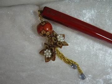 赤の漆にベージュと茶の二重巻きの落ち着いた小花で、金の鎖で華やかな作品です。