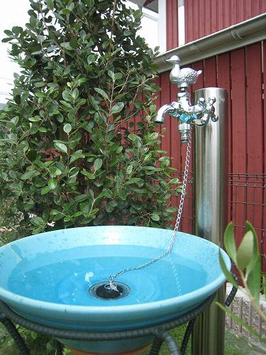 アイポイントに入れ込んだ鮮やかなトルコブルーの水鉢