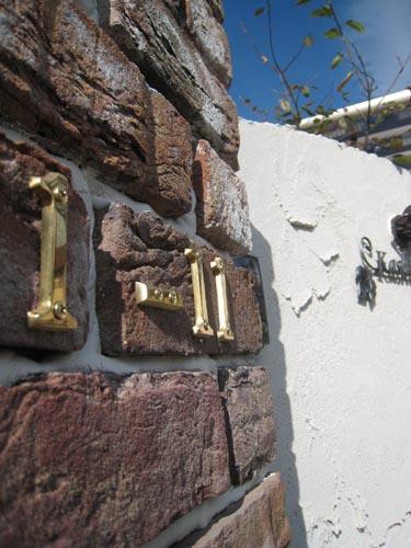 レンガの角柱には真鍮製のナンバーを使った住居表示。