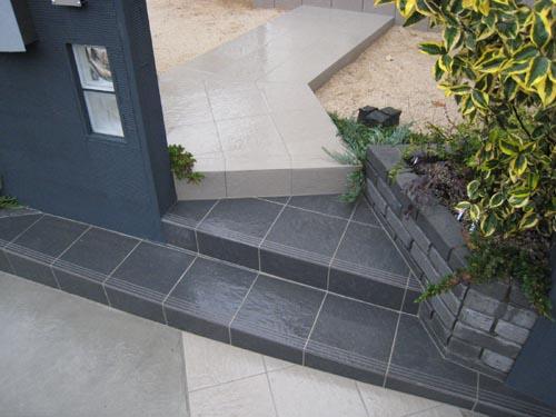 アプローチタイルもグレーとブラックの2色使い。門柱の間の階段部分のみが黒タイル。段鼻タイルのラインが直線を強調しています。