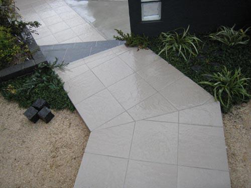角度をつけながら折れたタイルのアプローチ。階段の形状は鋭角になるようにデザインしています。このあたりの造型も格好良さを狙った設えなのです。
