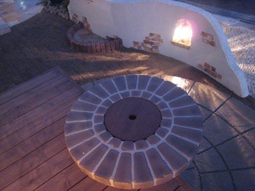 切り抜いたウッドデッキに円形状のバーベキューテーブル