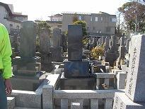 石塔と周りの石が後方に傾いてしまった墓地