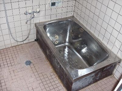 ステンレスの浴槽とタイルの床と壁