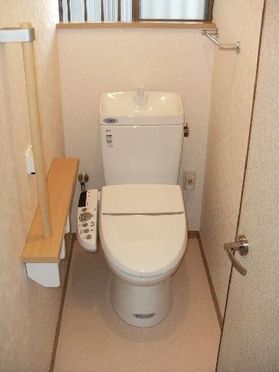 洋式トイレと手すりと棚がついた