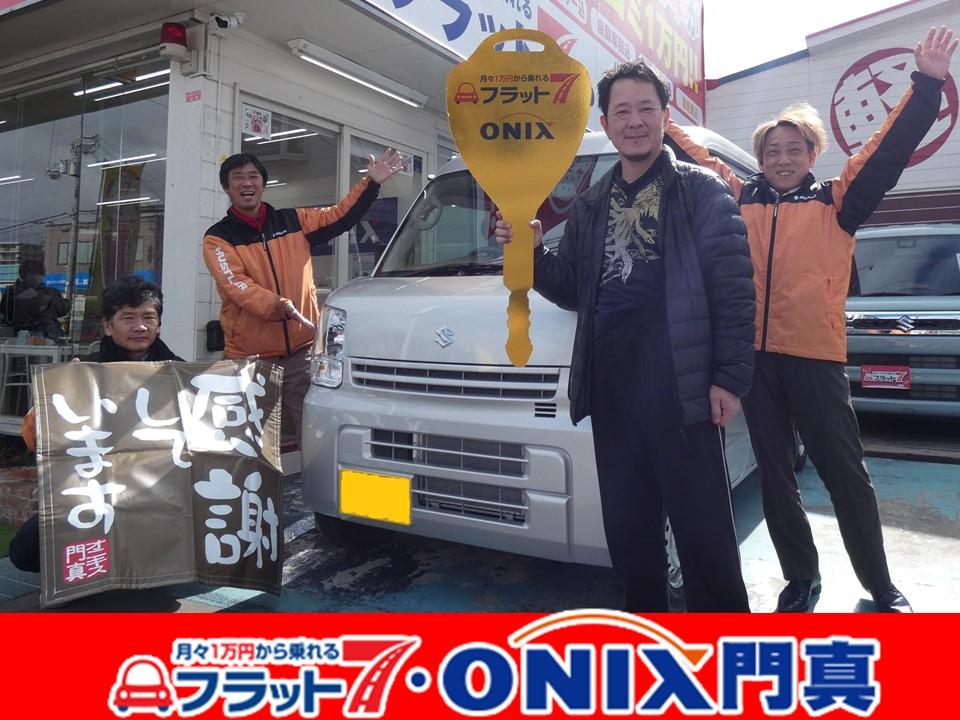 フラット7オニキス門真店納車式。『新車リース・フラット7』にて『エブリィバン』ご購入の大阪市鶴見区在住T様の笑顔です。